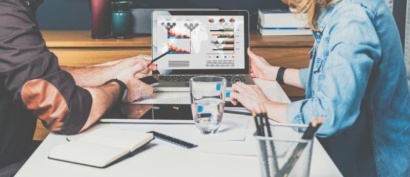 坐在膝上型计算机和工作前面的桌上的商人和女实业家 图表、图和图在个人计算机屏幕上 免版税库存照片