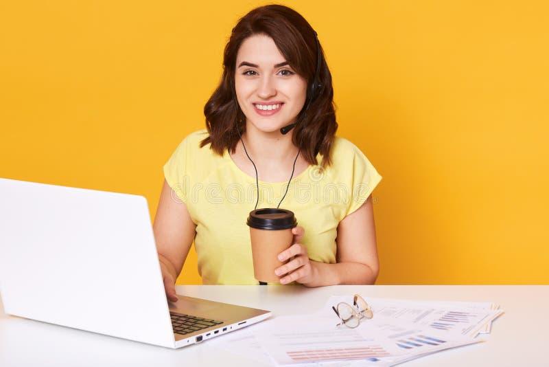 坐在膝上型计算机和饮用的外带的咖啡前面的白色书桌的俏丽的年轻女人从一次性杯子,女性佩带 免版税图库摄影