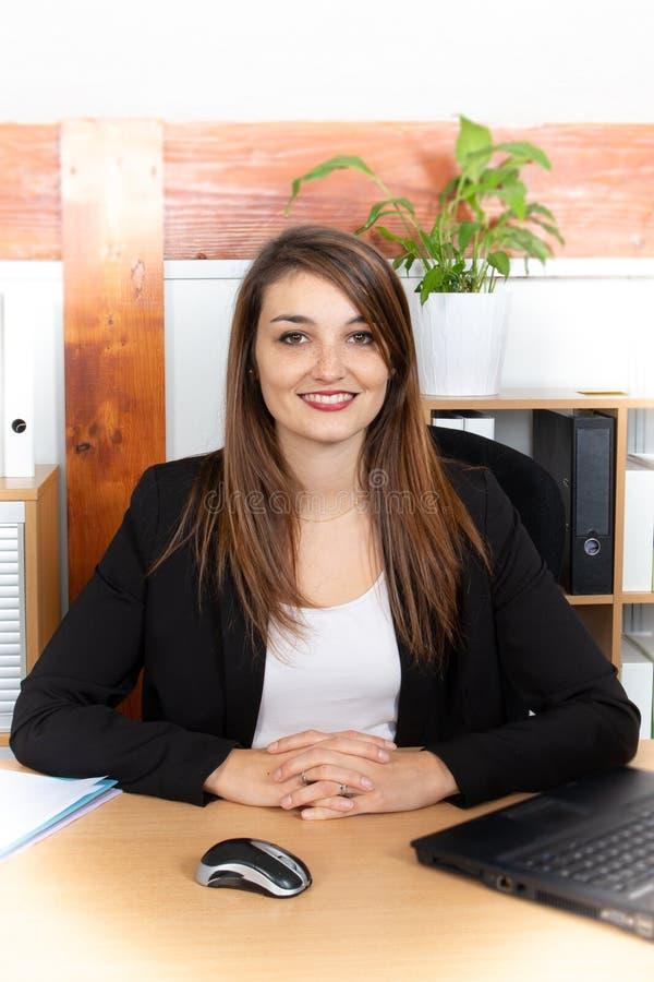 坐在膝上型计算机处理的事务前面的可爱的俏丽的年轻女实业家 免版税图库摄影