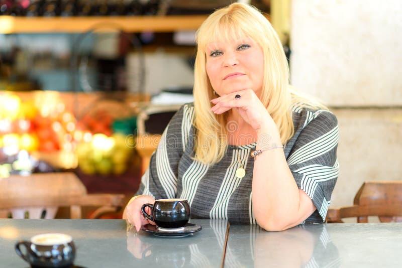 坐在自助食堂和看照相机的体贴的成熟妇女 放松中间年迈的妇女饮用的咖啡认为和 免版税库存照片