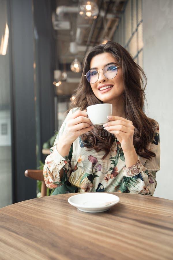 坐在自助食堂的体贴的微笑的妇女 库存照片