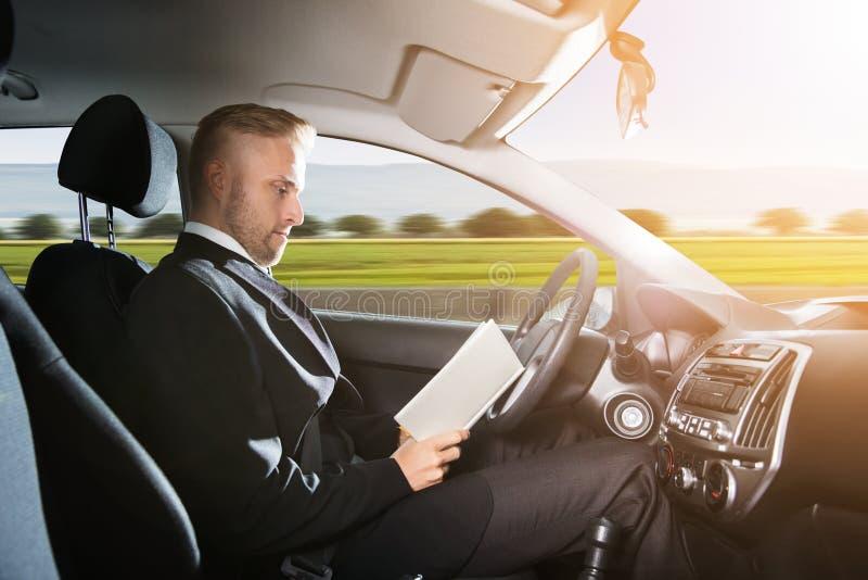 坐在自已里面的商人驾驶汽车 免版税库存图片