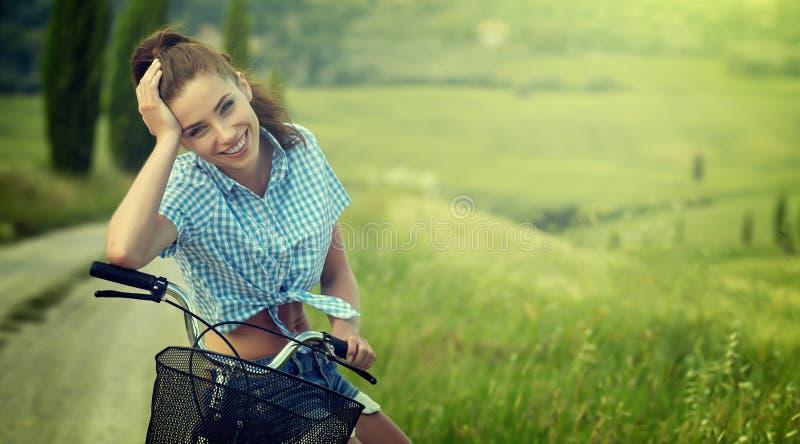 坐在自行车,夏时旁边的美丽的葡萄酒女孩 免版税图库摄影