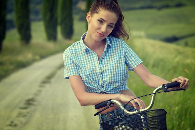 坐在自行车,夏时旁边的美丽的葡萄酒女孩 免版税库存照片