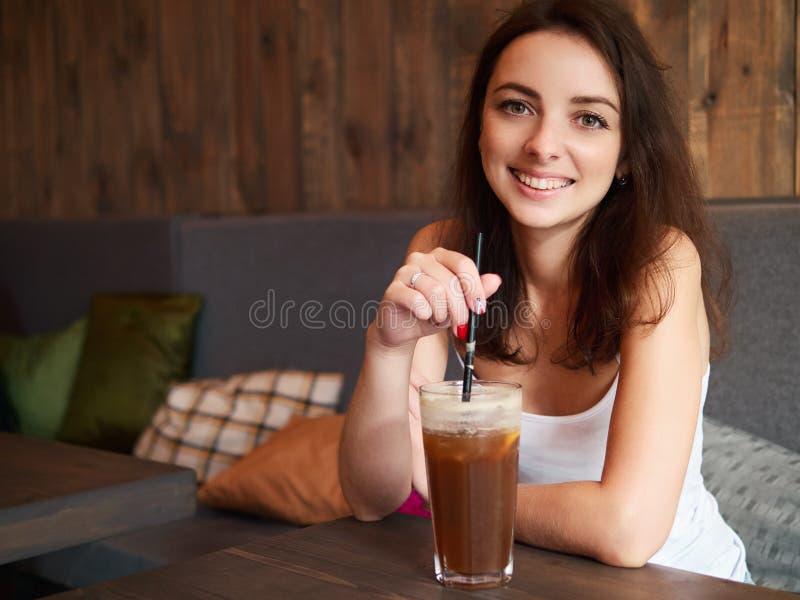 坐在舒适咖啡馆的美丽的逗人喜爱的深色的女孩在享用与秸杆和害羞微笑的窗口附近大杯子咖啡 库存图片