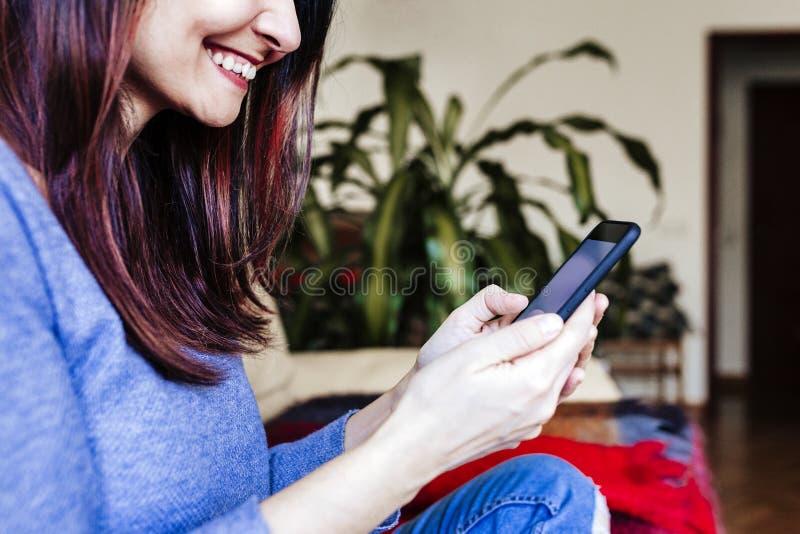 坐在舒适家庭沙发和使用现代智能手机设备,女性手的无法认出的年轻女人键入短信 社会 免版税库存图片