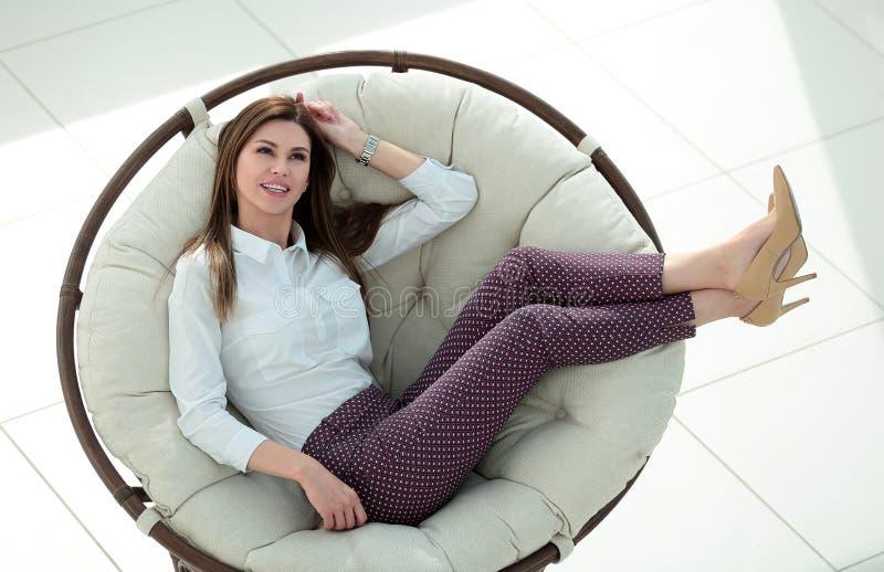 坐在舒适的圆的椅子的现代少妇 免版税库存照片