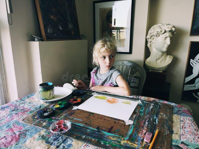 坐在艺术演播室的白种人学龄前儿童女孩集中与刷子和水彩油漆的绘的果子 库存照片
