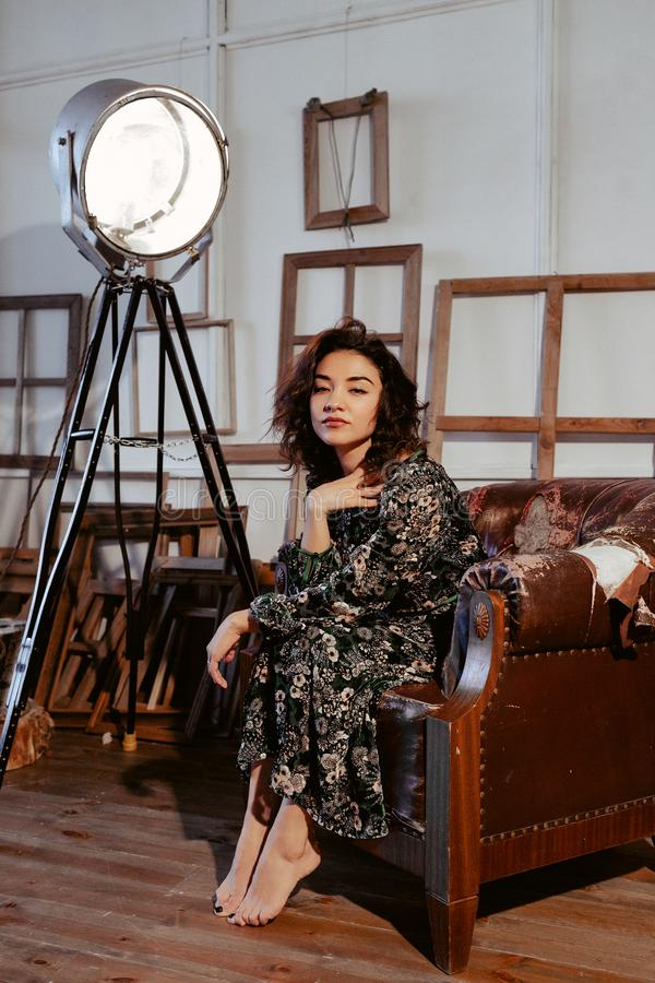 坐在花礼服的棕色椅子的美好的亚洲模型 库存照片