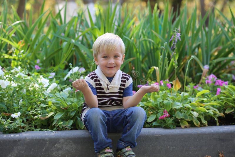 坐在花附近的小男孩 库存照片