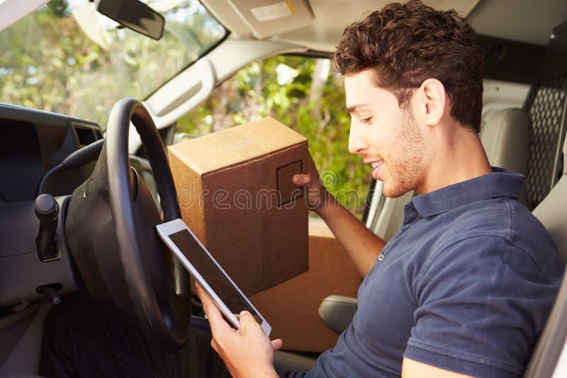 坐在范Using Digital片剂的交付司机 免版税库存照片