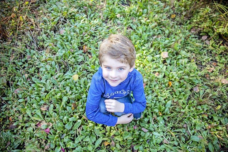坐在草外部的微笑的愉快的男孩 库存照片