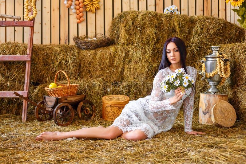 坐在草料棚的白色礼服的美丽的女孩 库存图片
