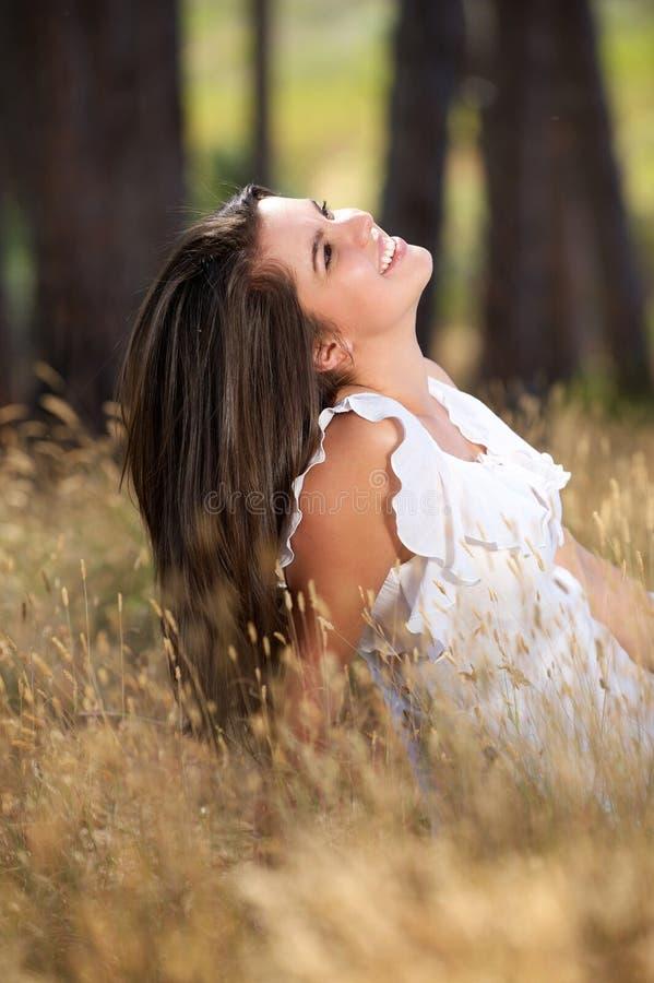 坐在草甸和微笑的愉快的少妇 图库摄影