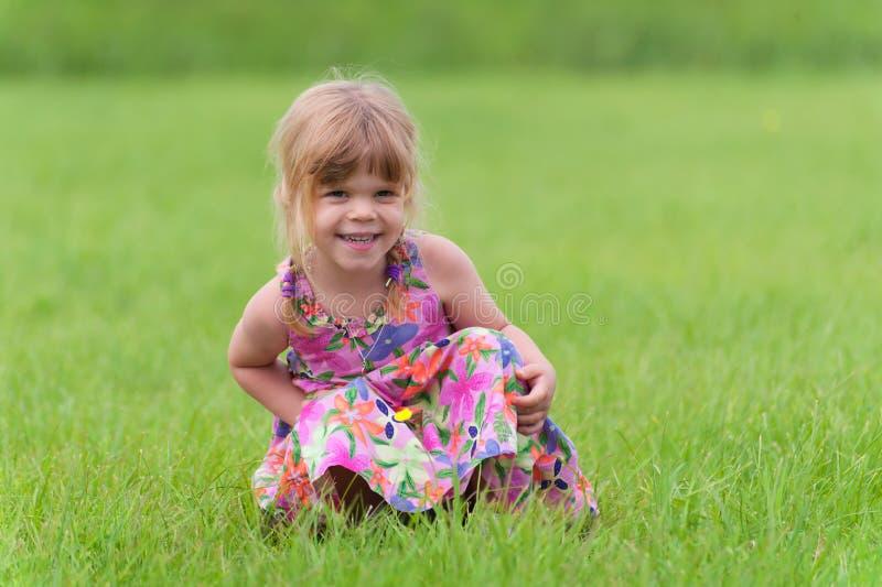坐在草的愉快的小女孩 免版税图库摄影
