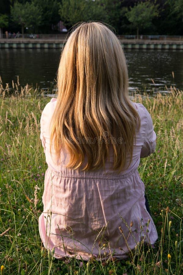 坐在草的白肤金发的妇女 库存图片
