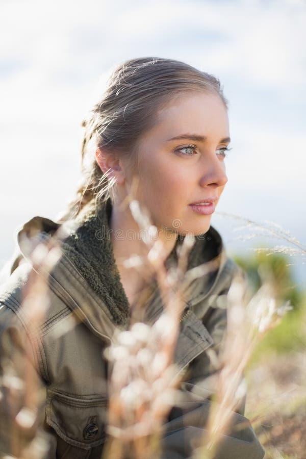 坐在草的美丽的妇女 图库摄影