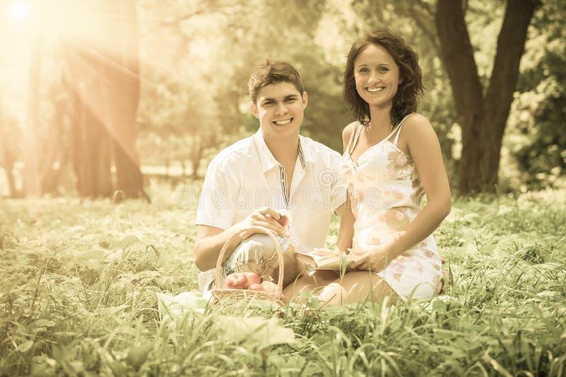 坐在草的美好的夫妇调查照相机微笑 免版税库存照片