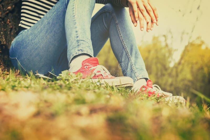 坐在草的蓝色牛仔裤和红色帆布运动鞋的妇女 免版税库存照片
