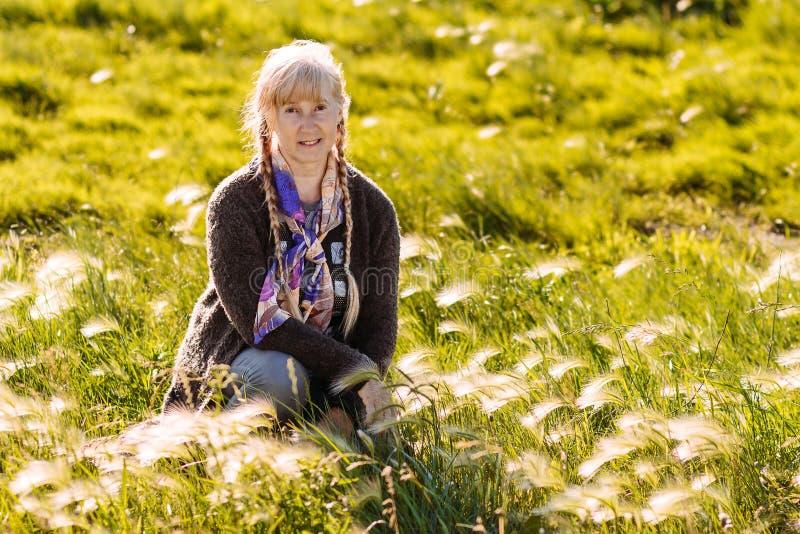 坐在草的50岁的白肤金发的妇女在夏天 免版税库存图片