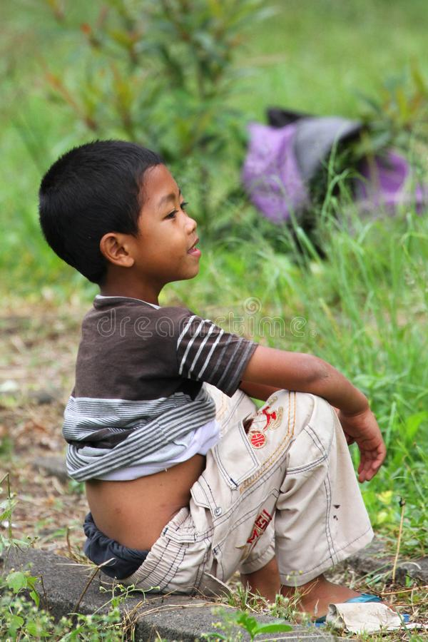 坐在草的Balianese男孩 图库摄影