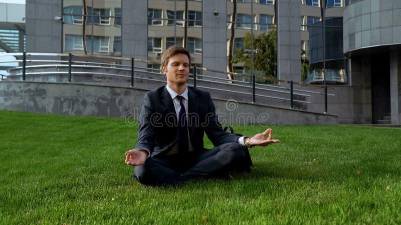 坐在莲花坐的商人,思考在草坪在办公室中心附近 免版税库存图片