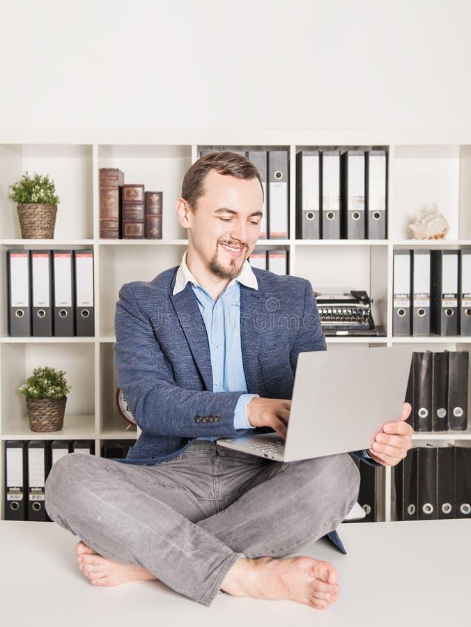 坐在莲花姿势和工作的愉快的英俊的商人 库存照片