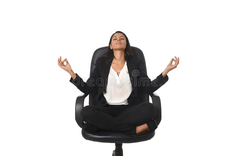 坐在莲花姿势实践的瑜伽的办公室椅子的年轻美丽的拉丁美洲的女商人 免版税图库摄影