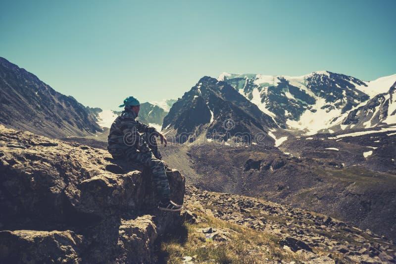坐在莲花姿势的少妇,思考,放松,赞赏的山在阿尔泰,西伯利亚 俄国 活跃生活概念和ide 免版税库存照片