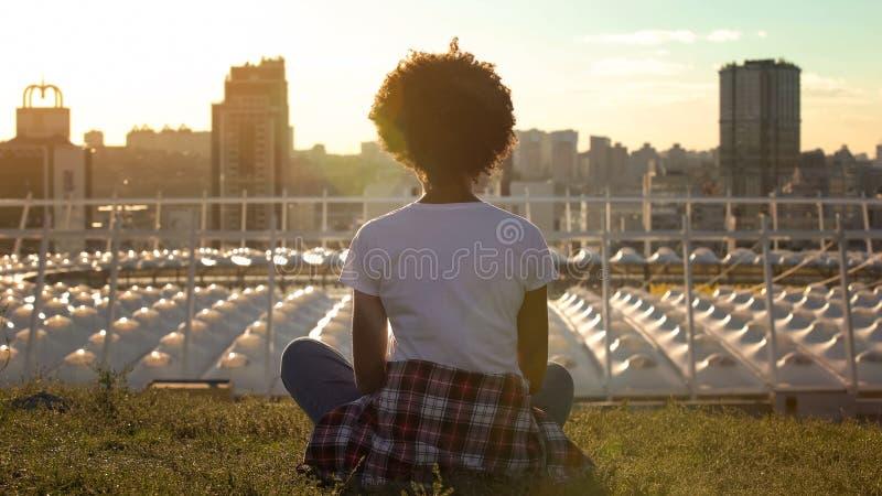 坐在莲花姿势的轻松的非裔美国人的妇女,思考在日落,休息 图库摄影