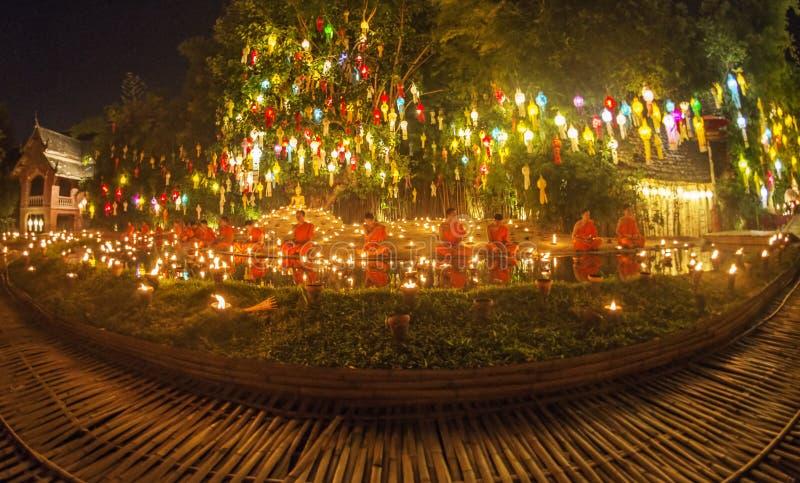 坐在菩萨雕象和举办的祷告附近的新手修士在伊彭节日,清迈,泰国 免版税图库摄影