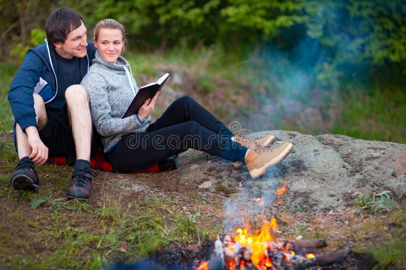 坐在营火和看书附近的愉快的年轻夫妇 免版税库存照片