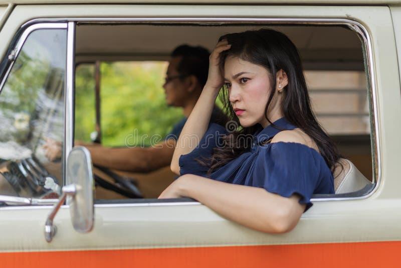 坐在葡萄酒汽车里面的被注重的妇女 免版税库存照片