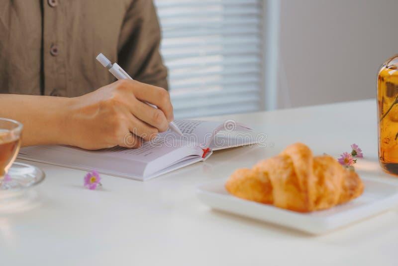 坐在葡萄酒白色木桌和茶上的一个人的播种的图象,当与笔记薄一起使用时 免版税库存照片
