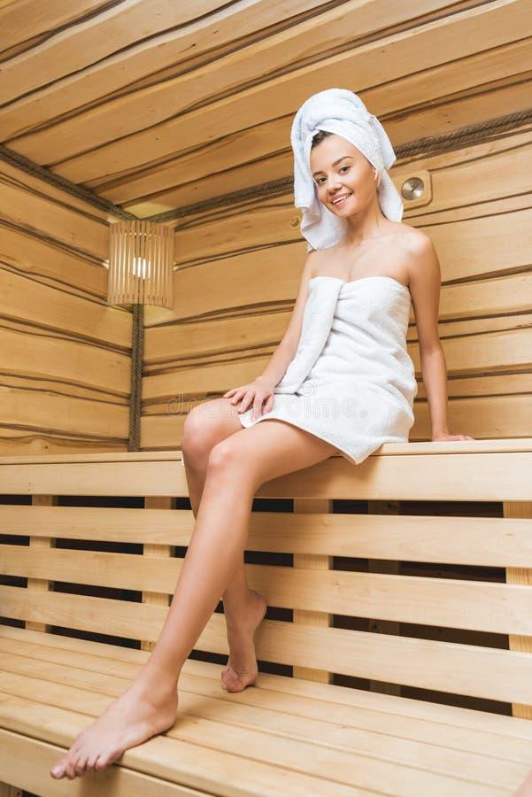 坐在蒸汽浴的可爱的少妇报道 免版税图库摄影