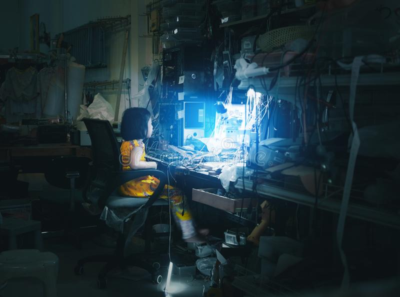 坐在蓝色屏幕显示器前面的女孩作为在计算机和电话维修车间服务的技术惯例与杂乱offi 免版税图库摄影