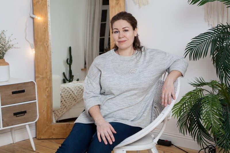 坐在藤条椅子的镇静可爱的妇女在镜子后的国内屋子里,看照相机 免版税库存图片