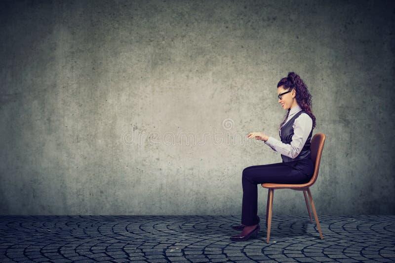 坐在虚构的桌上的妇女 免版税库存图片