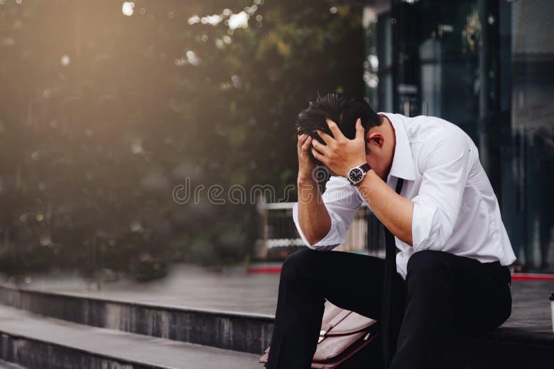 坐在行政管理部门的亚洲年轻商人重音用他的包括他的头的手反对 库存图片