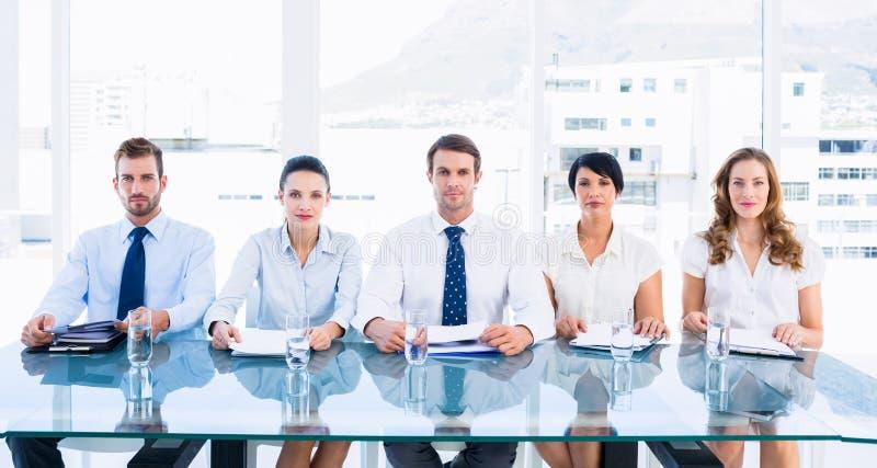 坐在行的聪明地加工好的董事在书桌 免版税图库摄影