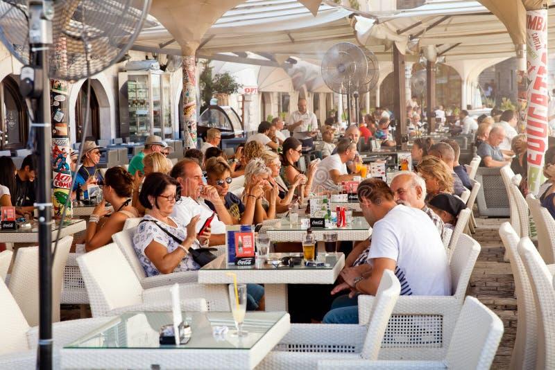 坐在街道咖啡馆和使用他们的小配件和智能手机的游人在老镇科托尔,黑山 免版税库存照片