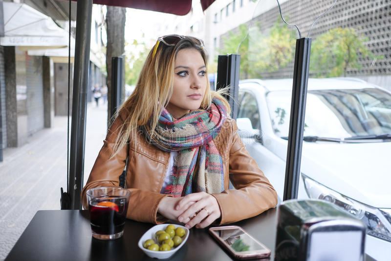 坐在街道咖啡馆的美丽的妇女画象 免版税图库摄影