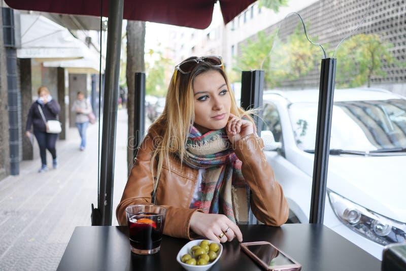 坐在街道咖啡馆的美丽的少妇画象  免版税库存照片