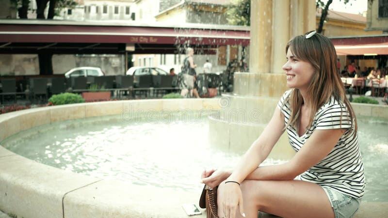 坐在街道喷泉附近的美丽的少妇 免版税库存照片