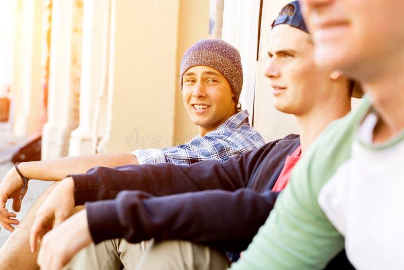 坐在街道的十几岁的男孩 库存照片