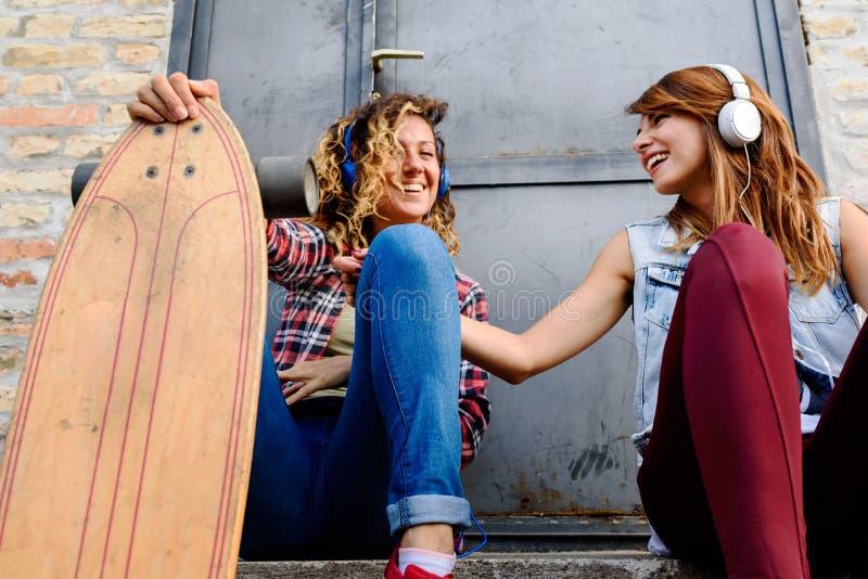 坐在街道的微笑的踩滑板的女孩垂悬听的音乐 库存图片