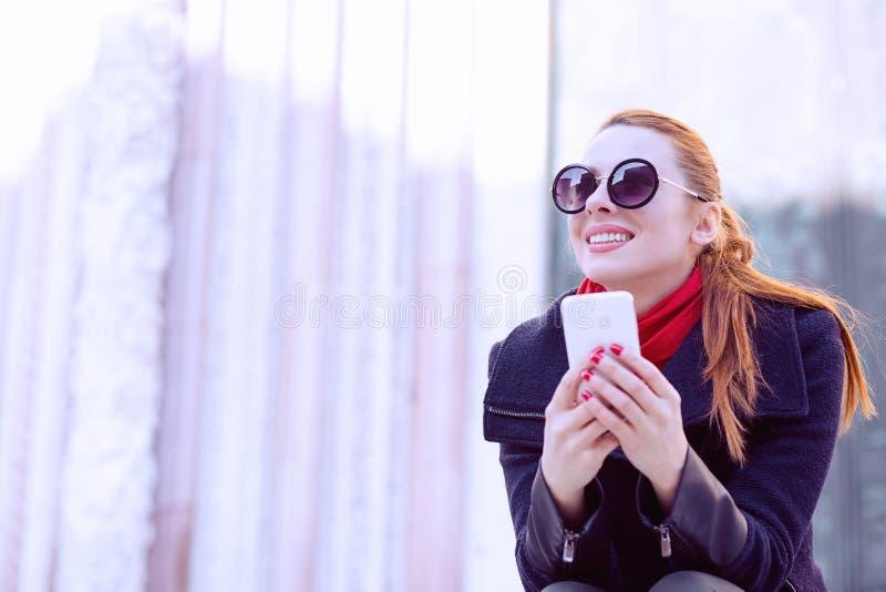 坐在街道的美丽的妇女举行她手机微笑 库存图片