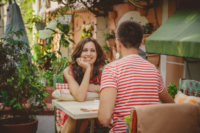 坐在街道露天咖啡馆的年轻美好的愉快的爱恋的夫妇看彼此 爱情小说起点  关系 免版税库存图片