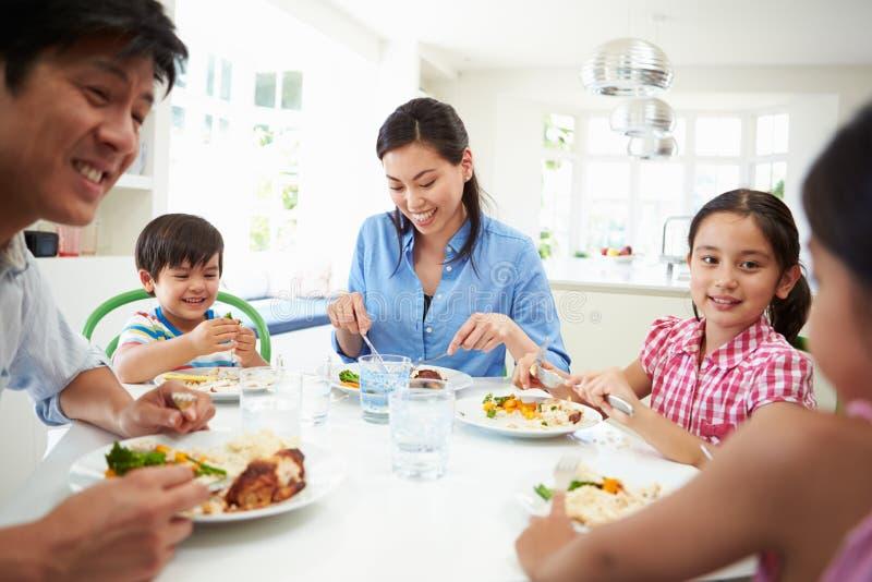 坐在表上的亚洲家庭一起吃膳食 免版税库存图片
