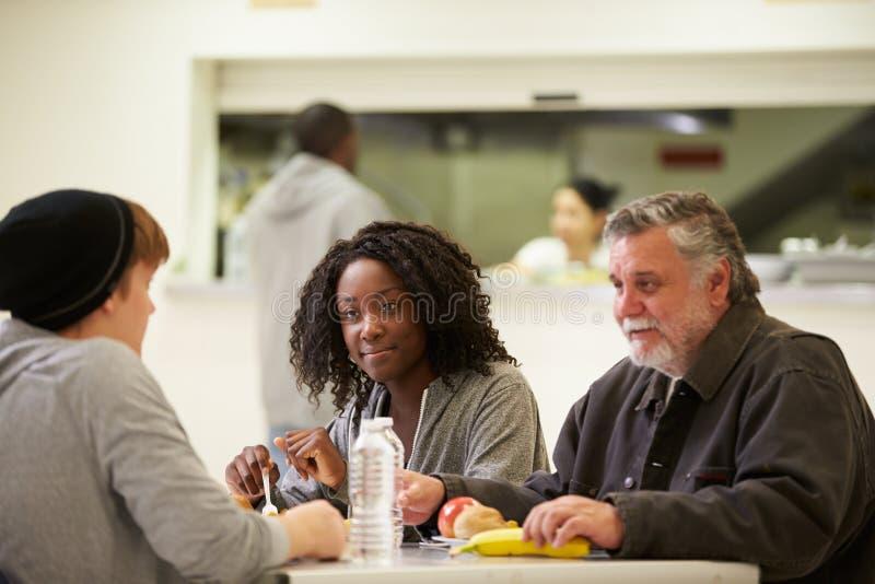 坐在表上的人们吃在流浪者避身处的食物 免版税图库摄影